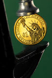 Financial pressure. Pinching a golden dollar coin in a c clamp  on green background (financial pressure concept Royalty Free Stock Image
