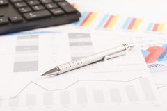 Financial printed paper charts, graphs on desk. With pen and keyboard Royalty Free Stock Image