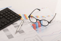 Financial printed paper charts, graphs on desk. With pen, mobile, glasses and keyboard Royalty Free Stock Image