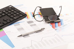 Financial printed paper charts, graphs on desk. With pen, mobile, telephone, glasses and keyboard Royalty Free Stock Image
