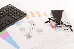 Financial printed paper charts, graphs on desk. With pen, mobile, telephone, glasses and keyboard Stock Images