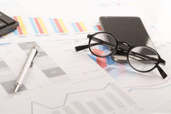 Financial printed paper charts, graphs on desk. With pen, mobile, telephone, glasses and keyboard Royalty Free Stock Images