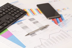 Financial printed paper charts, graphs on desk. With pen, mobile, telephone and keyboard Stock Images