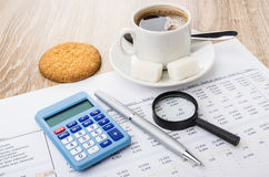 Financial printout, calculator, pen, magnifying glass, coffee an. D cookies on wooden table stock photo