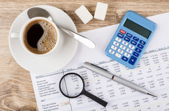 Financial printout, calculator, pen, magnifying glass and coffee. On wooden table. Top view stock photography