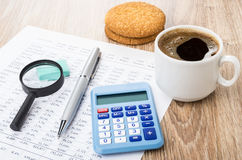 Financial printout, pen, magnifying glass, calculator, coffee an. D shortbread on wooden table stock image
