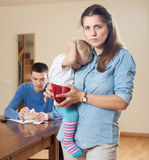 Financial problems in family. Sad women wit baby against husband with money Stock Photography