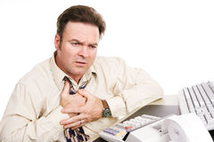 Financial Problems - Indigestion or Heart Attack. Businessman with financial problems experiencing indigestion or a heart attack. White background Royalty Free Stock Images