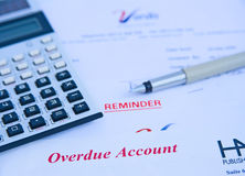 Financial problems: overdue account. A macro image with selective focus of a calculator and pen on an overdue account and another with reminder also in red text Stock Image