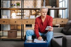 Serious retired man counting his savings Royalty Free Stock Image