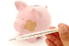 Financial prognosis. Thermometer reveals very high temperature with an 'injured' piggybank in the background Royalty Free Stock Photo