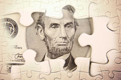 Financial puzzle. U.S. five dollars and puzzle pieces Stock Photography