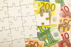 Financial puzzle. Puzzle with euro money under it for your financial or banking copy - lots of copy space in the puzzle Royalty Free Stock Photo