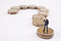 Financial Questioning Concept. Miniature businessman standing on quarters in shape of question mark Stock Images