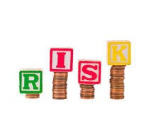 Financial R I S K and Pennies. Alphabet blocks spelling RISK on stacks on pennies Royalty Free Stock Photo