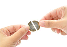 Financial recession. Two pieces of a broken coin being brought together stock photos