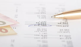 Financial report. Banknotes and pen on a paper of financial report Royalty Free Stock Images