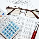 Financial report - calculator, glasses and papers stock images