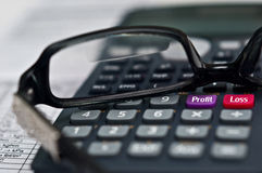 Financial report. A calculator with a profit and loss buttons with reading glasses on financial report royalty free stock image