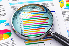 Financial report documents and magnifying glass Stock Images
