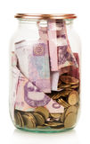 Financial reserves. Money conserved in a glass jar isolated on white Royalty Free Stock Images