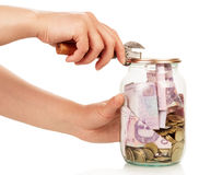 Financial reserves. Money conserved in glass jar opened by female hand isolated on white Stock Image
