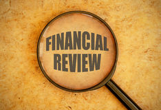 Financial review. Magnifying glass focused on the words financial review royalty free stock image