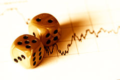 Financial risk. Dices on a stock market document - Financial risk concept - golden tone Stock Photography