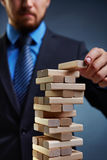 Financial risk. Business tower built by small wooden blocks royalty free stock images
