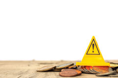 Financial risk. Coins falling and Warning label on whitebackgrou Royalty Free Stock Images