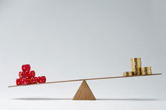Financial risk. Dice stack and money coins balancing on a seesaw Stock Photography