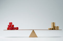 Financial risk. Dice stack and money coins balancing on a seesaw Stock Image