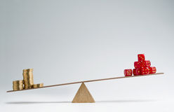 Financial risk. Dice stack and money coins balancing on a seesaw Royalty Free Stock Images