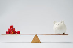 Financial risk. Dice stack and piggy bank balancing on a seesaw Stock Images
