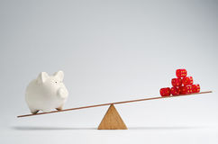 Financial risk. Dice stack and piggy bank balancing on a seesaw Stock Image