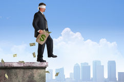 Financial Risk Success Plan Man Walking Off Building w Money. Blindfolded business man with bag of money is about to walk off the edge of a building representing Royalty Free Stock Image