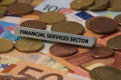 Financial services sector - the word was printed on a metal bar. the metal bar was placed on several banknotes Stock Image