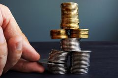 Financial Stability. Man holding coin in the coins stack. Royalty Free Stock Images