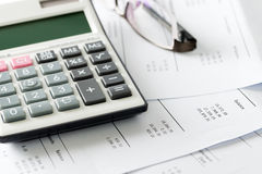 Financial statement with calculator and glasses Royalty Free Stock Photos