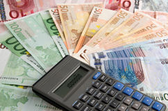 Financial statement. A calculator on many hundreds bank notes Stock Images