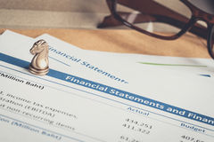 Financial statement letter on brown envelope and eyeglass, busin Stock Photos
