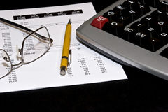 Financial statement and tools. An adding machine, mechanical pencil and reading glasses on a financial account statement Royalty Free Stock Photography