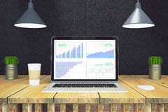 Financial statistics on laptop screen with paper cup of coffee o. N wooden table with black wall Stock Photo