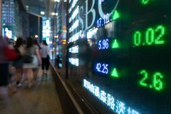 Financial stock exchange market display screen board on the street and city light reflection in Hong Kong. Financial stock exchange market display screen board stock photo