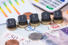 Financial stock word over graph and coins. And bank notes Stock Photography
