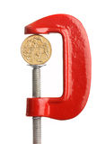 Financial strain. An Australian dollar coin in a clamp. Financial strain concept Stock Image