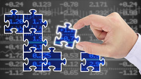 Financial success through a business plan concept. Hand putting pieces of a puzzle together revealing a blue glowing stock wall financial business success Royalty Free Stock Photography