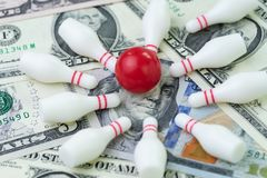 Financial success target concept, red winning bowling strike ball surround with knocked down pins on pile of US dollar banknotes. Money, goals on investment or stock images