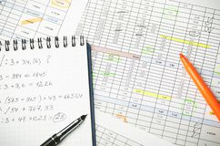 Financial tables on paper and notebook with calculations, pen and highlighter royalty free stock images