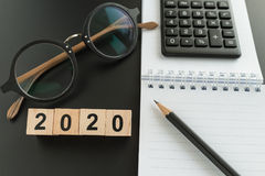 financial target or goal concept as selective focus on number 2020 wooden block with glasses, calculator, pencil, notebook stock photo